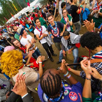 Scouter står i ring och klappar i händerna. Arkivbild från evenemanget Roverway 2012 som ordnades i Evo.