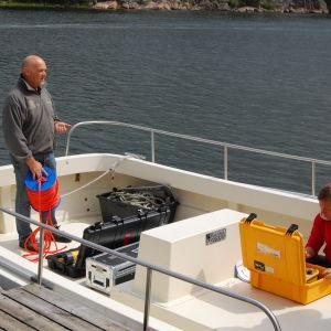 Kaksi tutkijaa noutavat mittauslaitteita veneellä.