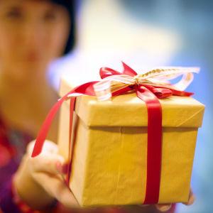 En kvinna håller upp en julgåva med sidenband.