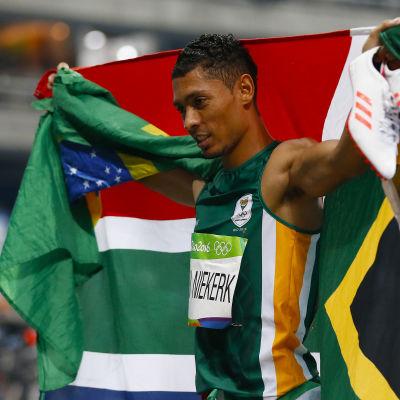 Sprinter håller upp den sydafrikanska flaggan efter guldlopp.