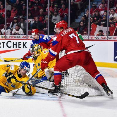 En svensk spelare ligger på isen framför eget mål. En rysk spelare försöker peta in pucken.