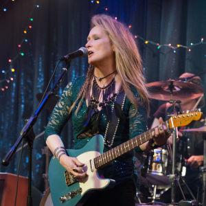 Meryl Streep rockar loss med en gitarr på scenen