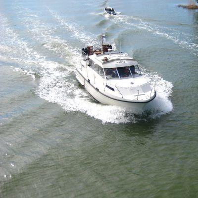 två båtar, en liten och en större som möts. Bilden fotad uppifrån.