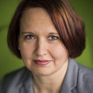 En mörkhårig kvinna i närbild med grön bakgrund.