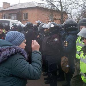 En kvinna gestikulerar och skriker åt en grupp kravallpoliser