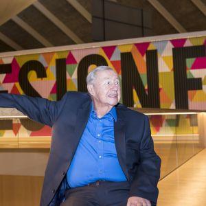 Terence Conran istuu museotilassa taustallaan teksti Designer