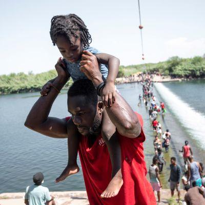 Människor går i vattnet i en flod i Texas. I förgrunden en man som bär sin lilla dotter på axlarna.