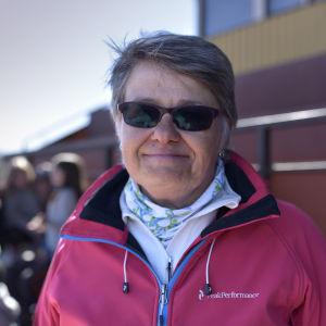 en kvinna med solglasögon och sportiga kläder ser mot kameran i publikläktaren på en idrottsbana
