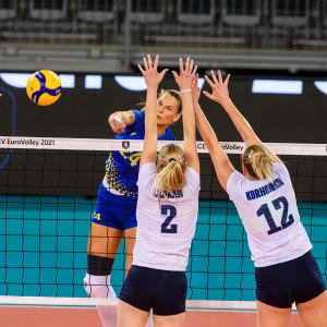 Finska volleybolldamer hoppar vid nätet.
