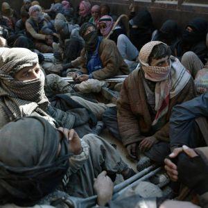 Män som lämnade IS sista fäste i Syrien och togs tillfånga sitter på ett lastbilsflak.