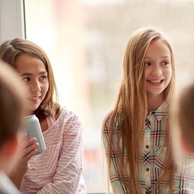 en skolflicka som ser blyg ut bland sina skolkamrater