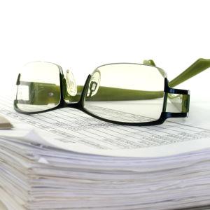 Ett par glasögon ligger på en hög med papper i en mapp.