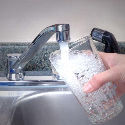 Människa tappar dricksvatten i glas
