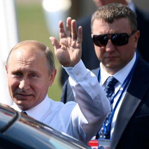 Bild på en vinkande Vladimir Putin