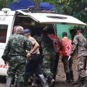 Räddningsarbetare lyfter in en av de räddade pojkarna i en ambulans