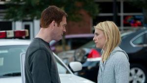 Man och kvinna framför en polisbil på gatan.