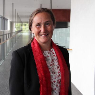 Porträtt på Arcadas rektor Mona Forsskåhl med korridor i bakgrunden.