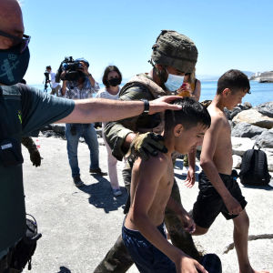 Sotilaat taluttavat maahan pyrkivää lasta Espanjan rannikolla.