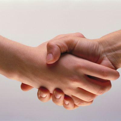Kättely. Kaksi kättä puristaa toisiaan.