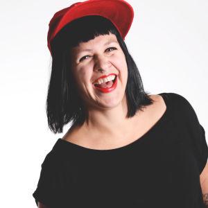 Catariina Salo: Tjej med svart hår och pannlugg, som har en röd keps och en svart t-shirt på sig.