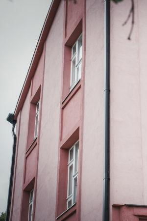 Vaalenapunainen kivitalo valkoisine ikkunanpuitteineen.