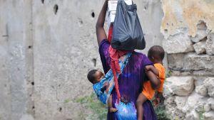 Somalisk kvinna bär sina två barn och saker.