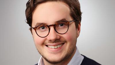 Man med brunt hår, bruna glasögon ler mot kameran