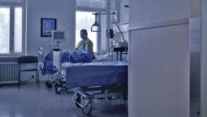 Nainen istuu sairaalasängyllä.