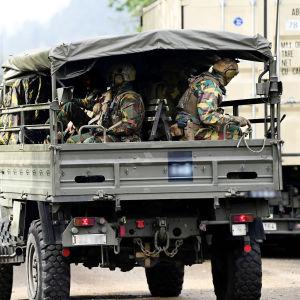 Aseistautuneita sotilaita sotilasajoneuvossa.