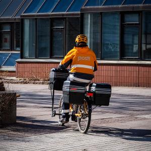 Postinjakelija jakaa postia polkupyörällä.