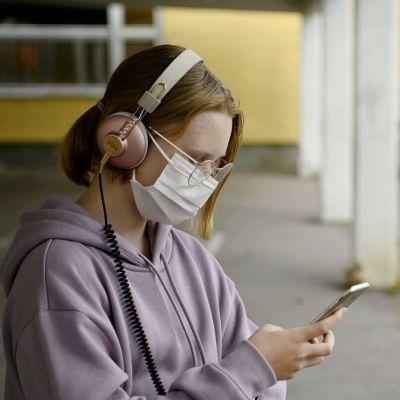 Ung kvinna med munskydd håller en mobiltelefon i handen.