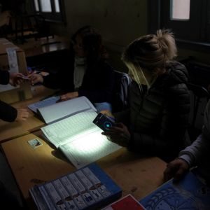 En valfunktionär använde sin mobiltelefon för att lysa upp sina papper i en vallokal i Rosario. Trots strömavbrottet genomfördes regionalval i delar av Argentina på söndagen.