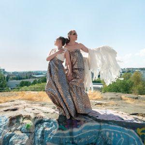 Marja Ahlsved och Heidi Kiviharju från Arosa Ensemble står iklädda klänningar på en klippa i en stad.