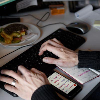 Työntekijä kirjoittaa työpöytänsä ääressä.