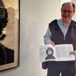 Heikki Kastemaa näyttää kirjan aukeamaa Kumu-taidemuseossa.