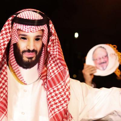 En demonstrant iklädd en mask som föreställer kronprins Mohammed. Bild på Khashoggi i bakgrunden. Denhär demonstrationen hölls utanför Saudiarabiens konsulat i Istanbul den 25 oktober.