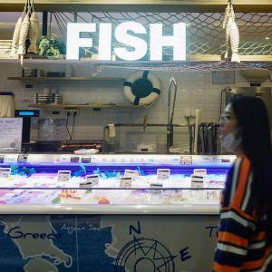 Kvinna vid en frysdisk i en livsmedelsbutik i Kina