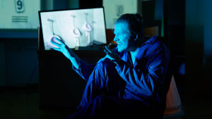 Näyttelijä Juho Uusitalo istuu lattialla työhaalarissaan, kuvassa on sininen valo, taustalla on televisio jossa näkyy kuva koulun poikien vessasta.