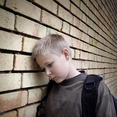 Nedstämd pojke som lutar sig mot väggen.