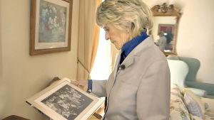 Jean Kennedy katselee perhekuvaa