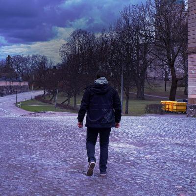 Mies kävelee Suomenlinnassa selkä kameraan päin