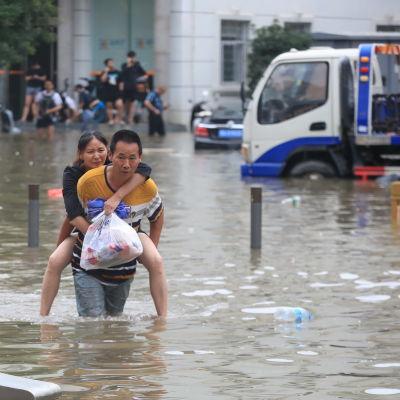 En man bär en kvinna på ryggen i ett översvämmat Zhengzhou.