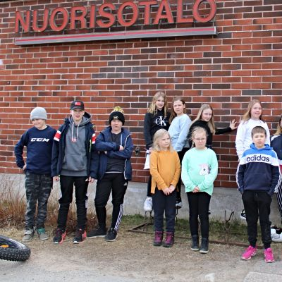 Kymmenkunta lasta ja nuoriso-ohjaaja Laura Huhta seisovat Ylitornion nuorisotalon edessä.
