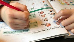 Barn som gör läxa i finska språket.