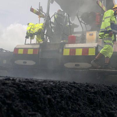 Kone levittää uutta asfalttia.