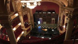Kungliga Operans praktfulla scen med kristallkrona och förgyllda pelare och detaljer.