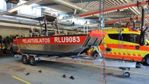 en röd och silverfärgad aluminiumbåt på en trailer inne i en brandstation. Står pelastuslaitos längs båtens långsida. I bakgrunden en gul-orange ambulans eller räddningsbil.