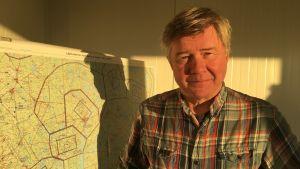 En medelålders man tittar in i kameran. Han står inomhus framför en karta. Kvällssolen lyser honom i ansiktet med ett gult sken.