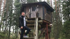 Mats Grönholm klättrar upp i en stuga uppe i ett träd