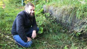 John Björkman sitter på huk vid Bläsnäs källa i Pargas
